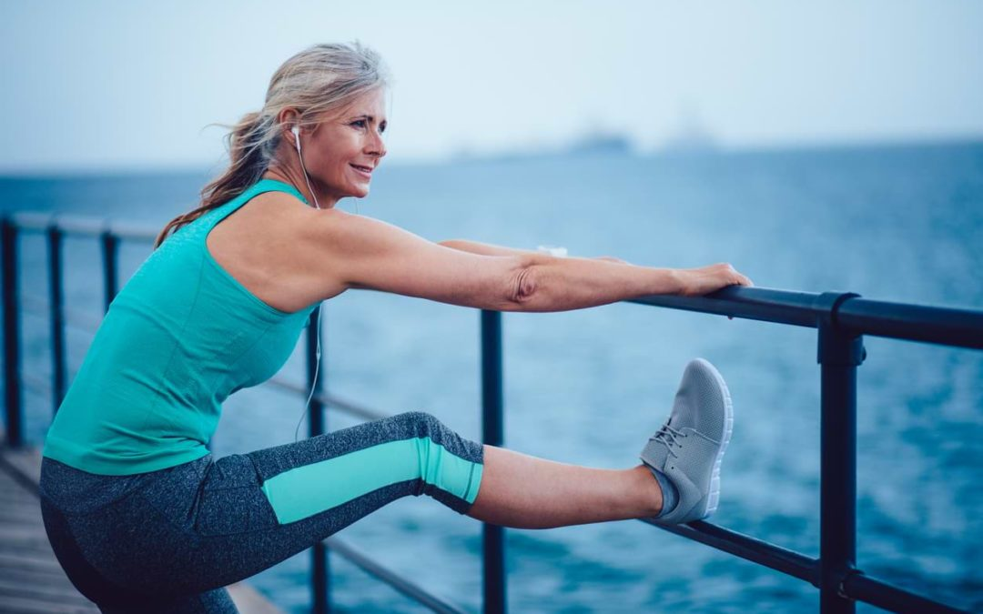 woman stretching and exercising legs on pier